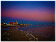 New Art Titled: Dawn over the Daytona Beach Coast Line. Digital art edit of photograph taken at dawn from the northern edge of Daytona Beach Shores to the white spot in the distance, which is the Pier at Main Street in Daytona Beach, Florida.
