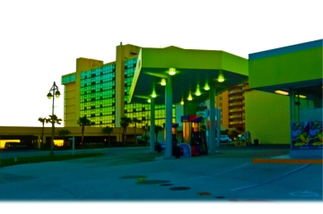 New Art Release Titled; Gas Food and Beach Lodging. Gas station with lights on, the corner of a small shopping center, an ocean side resort with a double layer parking garage, lines with palm trees and a condominium